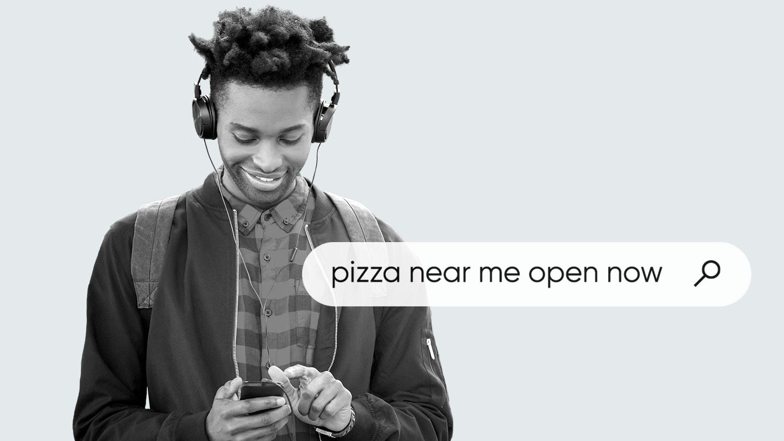 ヘッドフォンをつけ、携帯電話を使用して現在営業中の「近くのピザ屋」を検索する男性